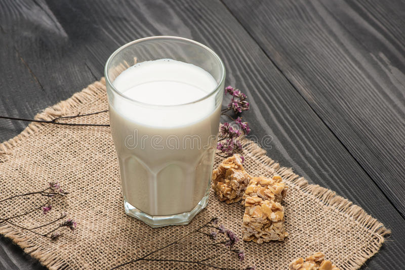 Prodotti lattier-caseario Un servire del bicchiere di latte con le caramelle della mandorla su una r fotografie stock libere da diritti