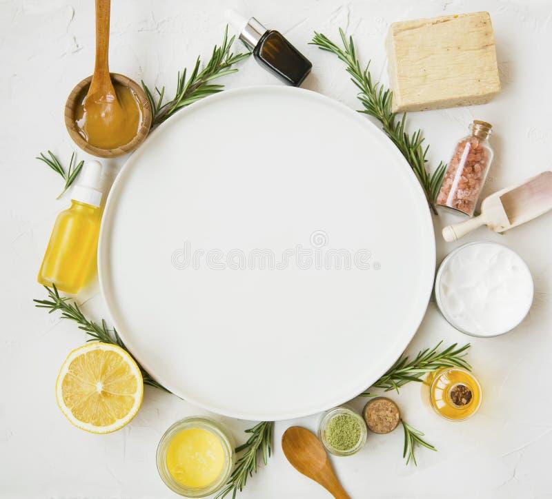 Prodotti naturali dello skincare con i petroli, le erbe, il miele di manuka e lo spazio rotondo della copia del piatto fotografia stock libera da diritti