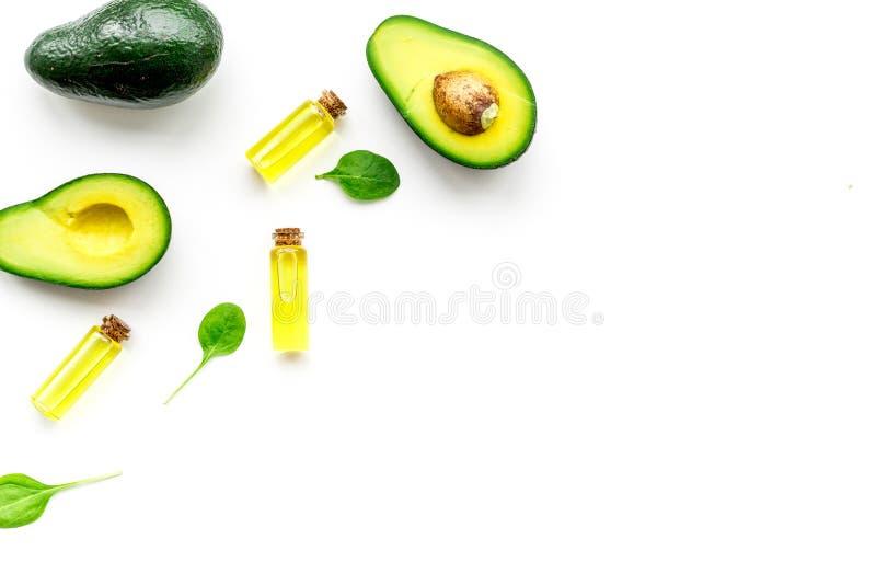 Prodotti naturali per cura di pelle L'olio di avocado in bottiglie vicino ha affettato l'avocado sullo spazio bianco della copia  fotografie stock