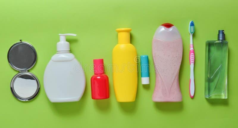 Prodotti per bellezza, autosufficienza e igiene su un fondo pastello verde Sciampo, profumo, rossetto, gel della doccia, spazzoli fotografie stock libere da diritti