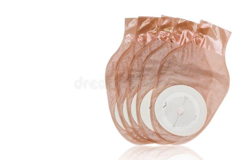 Prodotti scaricabili di un pezzo del sacchetto della colostomia o di ileostomy isolati su fondo bianco Cinque prodotti di cura de immagini stock libere da diritti