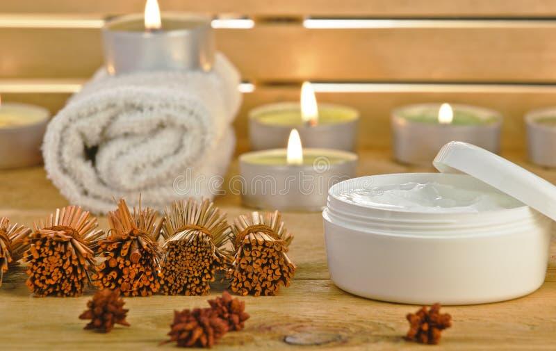 Prodotto crema cosmetico con le candele su di legno. fotografia stock