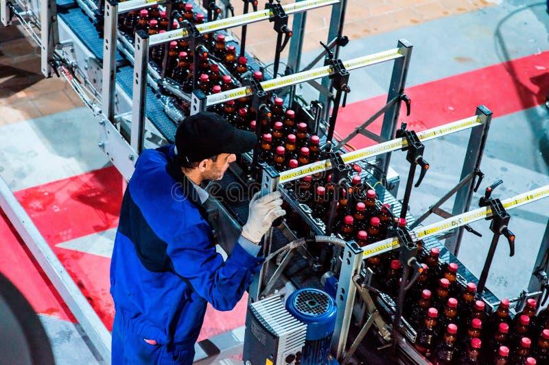 Produção da cerveja da garrafa com trabalhador fotografia de stock