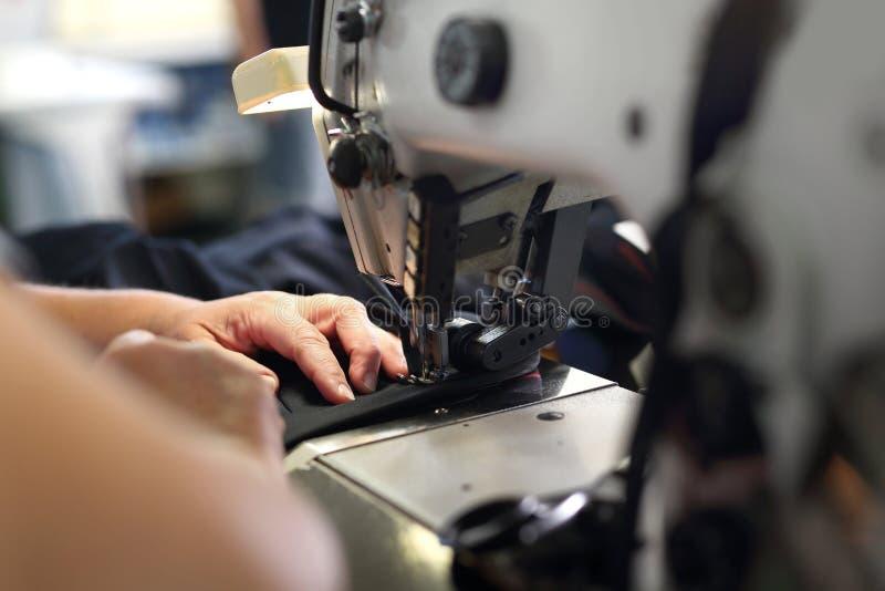 Produção de roupa, costurando em uma máquina imagem de stock