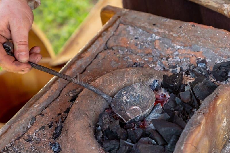 A produção tradicional de metal de prata líquido do trabalho do ferreiro derrete em uma colher preta de couro em carvões ardentes fotos de stock royalty free