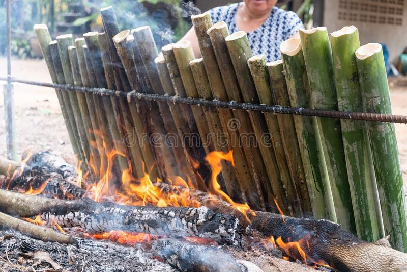 Produca il riso glutinoso con latte di cocco arrostito in un cilindro di bambù dei giunti di lunghezza, fuga di Khao è dessert do fotografia stock