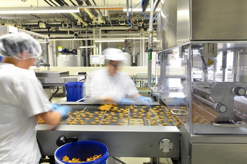 Producción de almendras garapiñadas en una fábrica para la industria alimentaria - wome fotografía de archivo libre de regalías