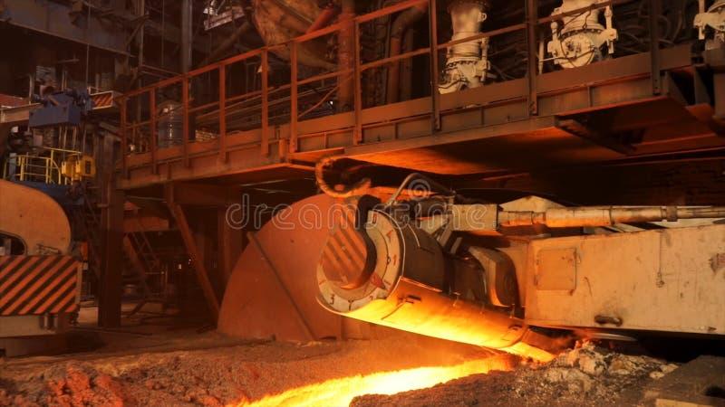 Producción de fundición en la fábrica, concepto de la metalurgia Cantidad común Acero fundido que fluye en canal inclinado metalú imagen de archivo