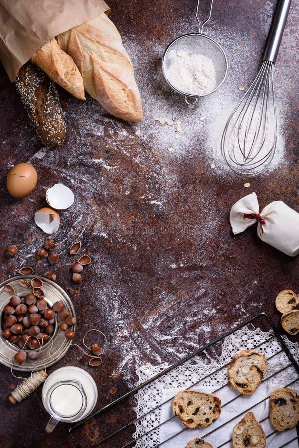 Producción de la panadería - pan, baguette, galletas sobre fondo rústico Ingredientes de la hornada - harina, nueces, huevos, lec imagenes de archivo