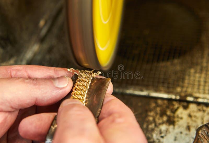 Producci?n de la joyer?a El joyero pule una pulsera del oro foto de archivo