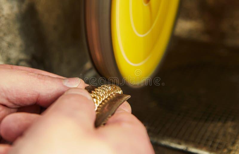 Producci?n de la joyer?a El joyero pule una pulsera del oro imagen de archivo