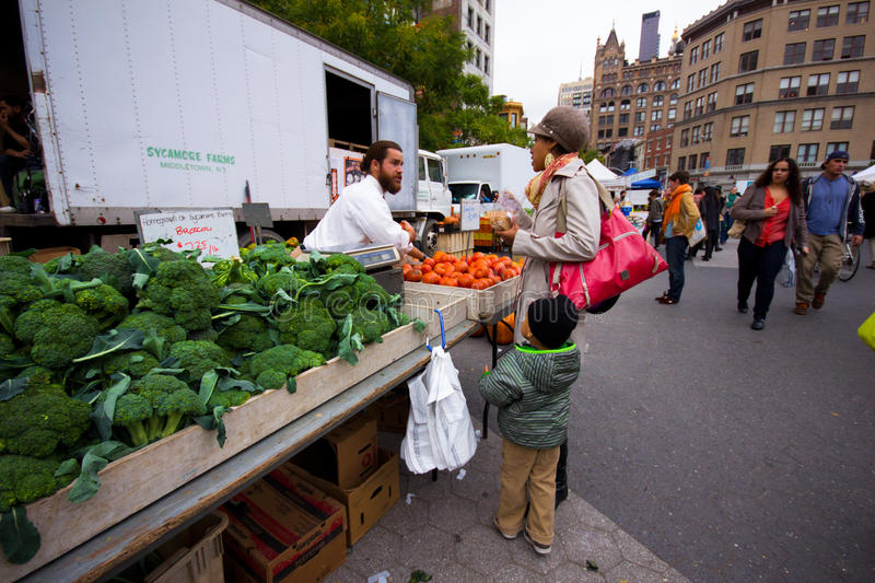 Produce Sale NYC. NEW YORK CITY - OCT 26: Woman selects produce at Union Square Greenmarket in NYC on Oct. 26, 2012. This world famous farmers' market began in stock photos