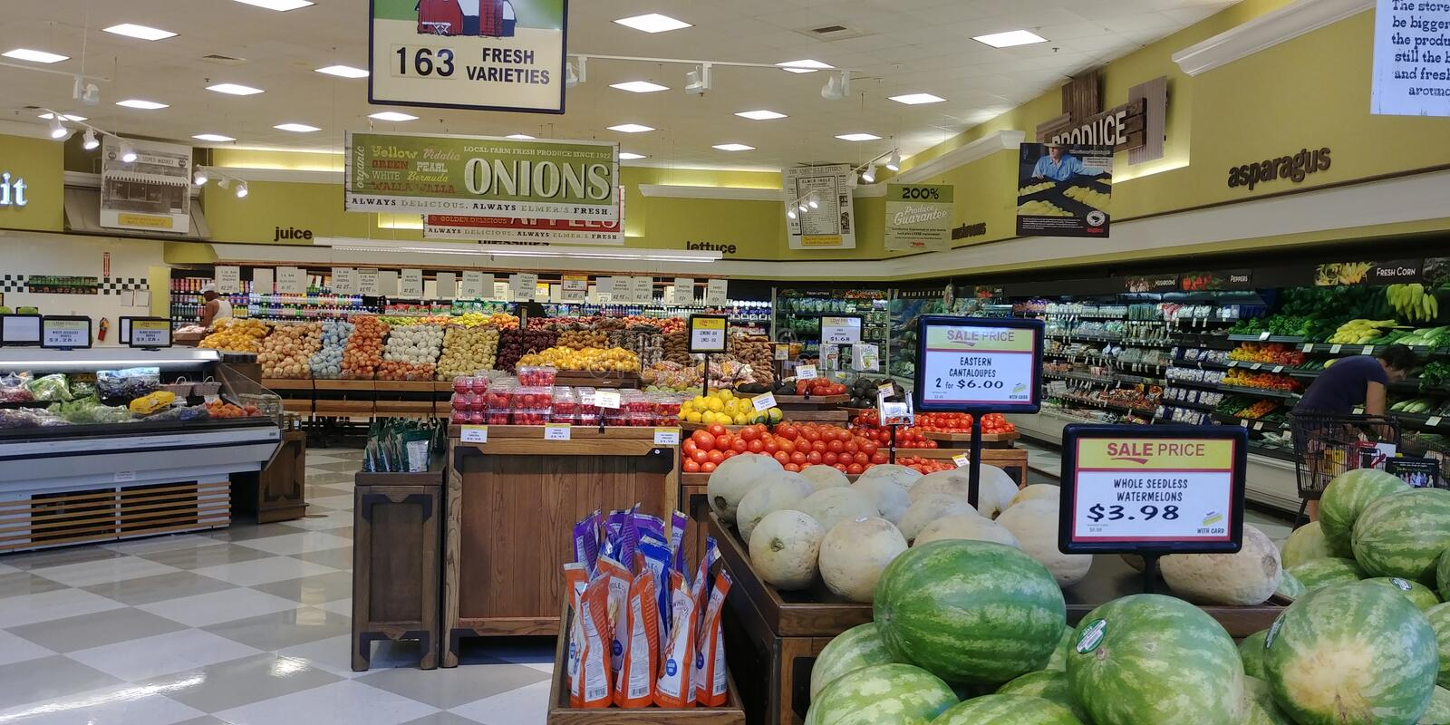 Produce are in supermarket. Produce area of supermarket showing watermelon, cantaloupe, tomatoes, onions. Sale price signs royalty free stock image