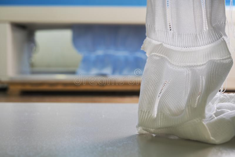 Piece of produced knitted fabric shot. Produced piece of white knitted fabric view at a knitting shop stock photos
