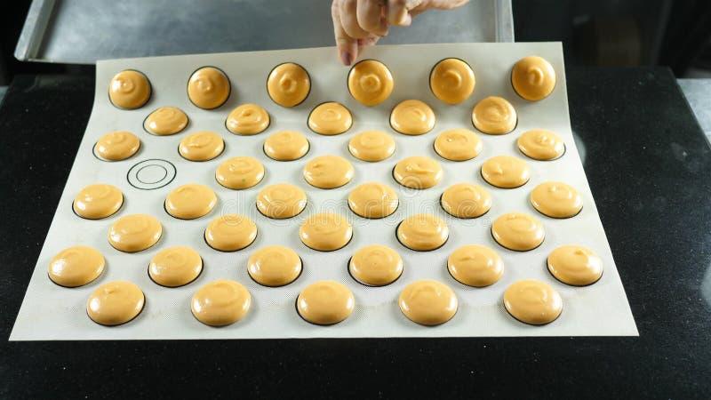 Producendo il maccherone del macaron, dessert francese, schiacciante la forma della pasta che cucina borsa fotografia stock libera da diritti