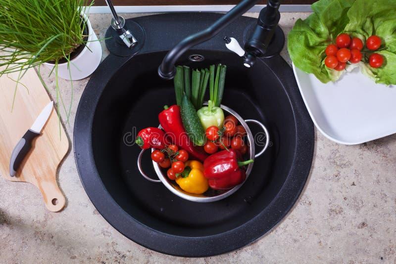 Producendo un'insalata di verdure - lavare gli ingredienti immagini stock