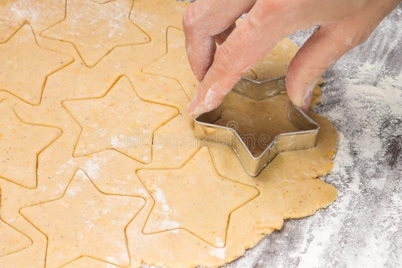 Producendo zenzero impanare i biscotti di natale con la taglierina del metallo Pasta e farina dello zenzero fotografia stock