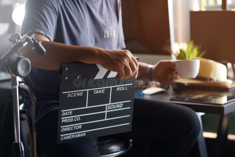 Producent eller kameraman sitter i barstolar och håller filmskiva av klapper eller skifferfilm och kaffe på dricksmorgen Kaffebro arkivbild