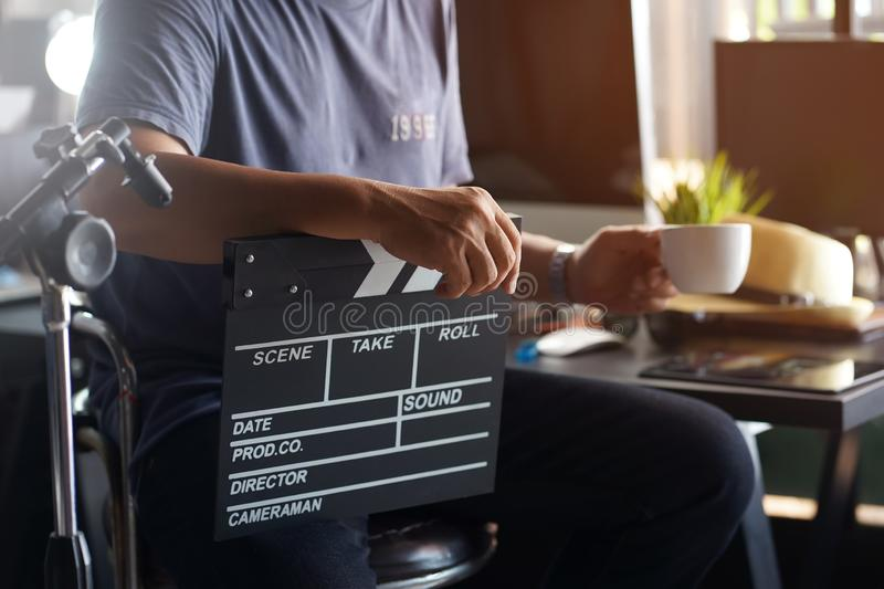 Producer or cameraman sit on Bar Chair and holding clapper cinema board or Slate film and drinking morning coffee.Coffee break at. Studio stock photography