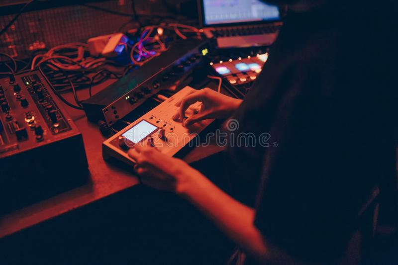 Producer  DJ mixer in a nightclub with glowing plays musical rave Dubstep Electronic Trance composition with modern midi controlle royalty free stock photo