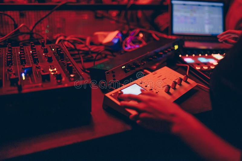 Producer  DJ mixer in a nightclub with glowing plays musical rave Dubstep Electronic Trance composition with modern midi controlle. DJ mixer in a nightclub with stock photography