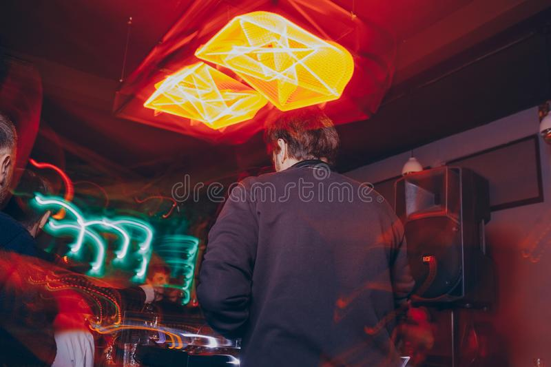 Producer  DJ mixer in a nightclub with glowing plays musical rave Dubstep Electronic Trance composition with modern midi controlle. DJ mixer in a nightclub with royalty free stock photography