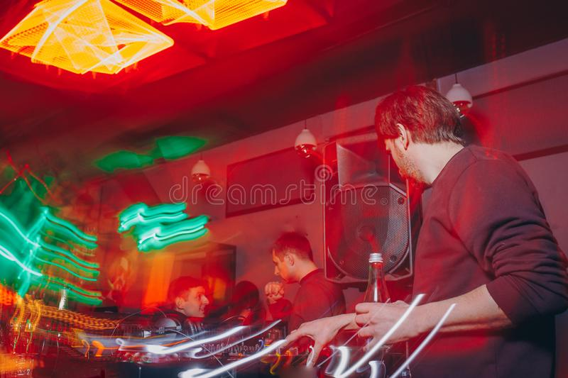 Producer  DJ mixer in a nightclub with glowing plays musical rave Dubstep Electronic Trance composition with modern midi controlle. DJ mixer in a nightclub with stock photos