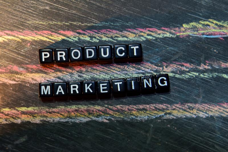 Product Marketing on wooden blocks. Cross processed image with blackboard background. Inspiration, education and motivation concepts stock image
