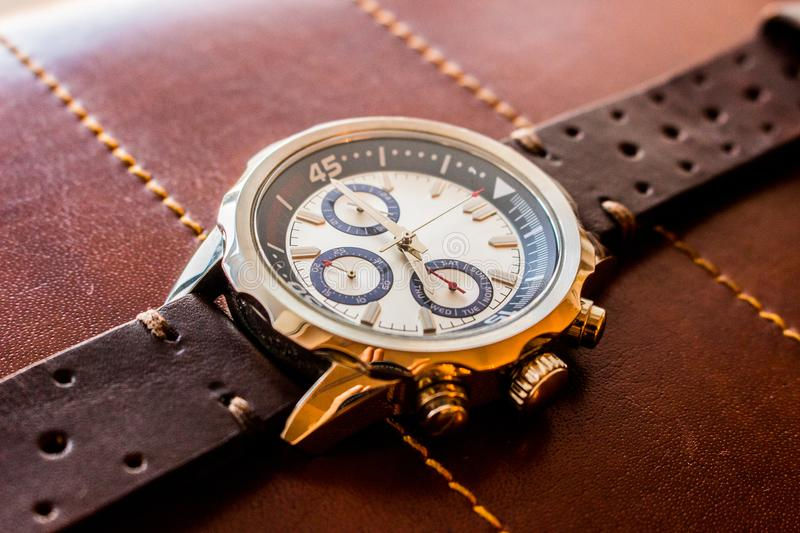 Luxury wrist man watch with leather strap showing time. Product photography of a luxury man wrist watch showing time on leather material background stock photography
