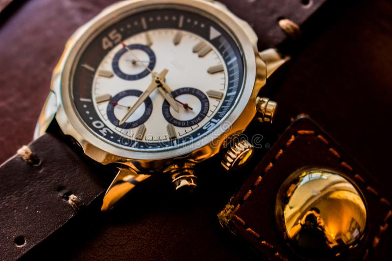Wrist man watch showing time. Product photography of a man wrist watch showing time on leather background royalty free stock photo