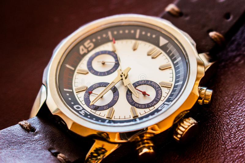 Wrist man watch showing time. Product photography of a man wrist watch showing time on leather background stock image