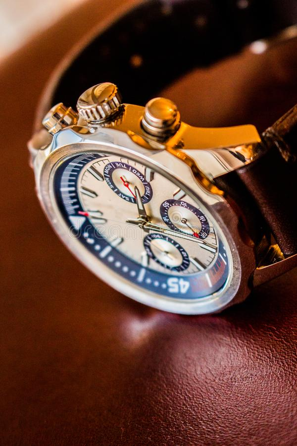Wrist man watch showing time. Product photography of a man wrist watch showing time on leather material background royalty free stock images