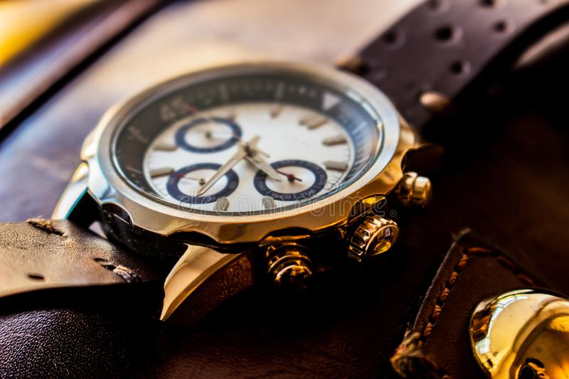 Wrist man watch showing time. Product photography of a man wrist watch showing time on leather material background stock image