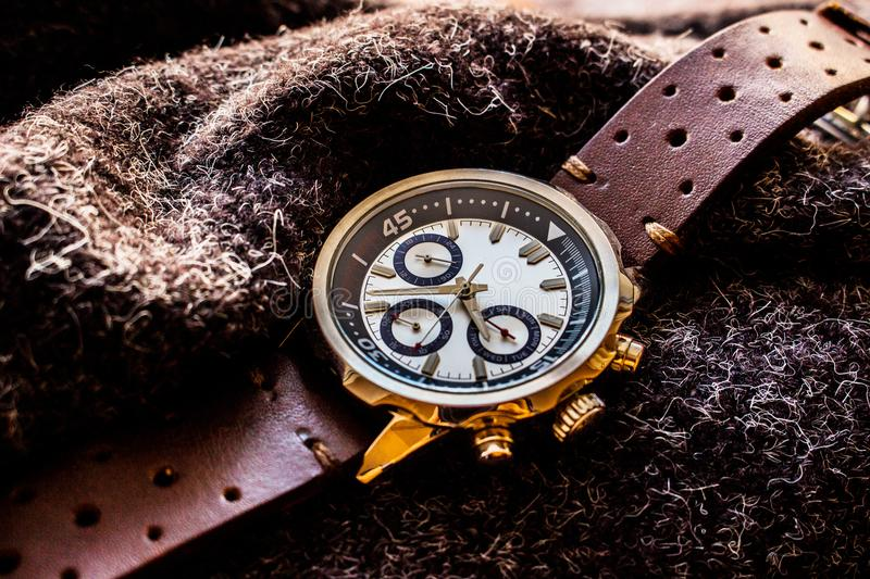 Wrist man watch showing time. Product photography of a man wrist watch showing time on wool material royalty free stock photo