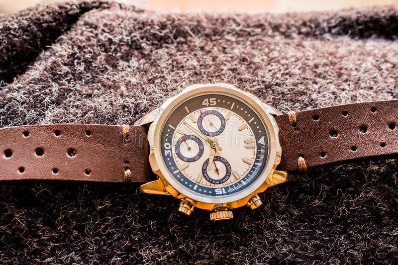 Wrist man watch showing time. Product photography of a man wrist watch showing time on wool material stock images