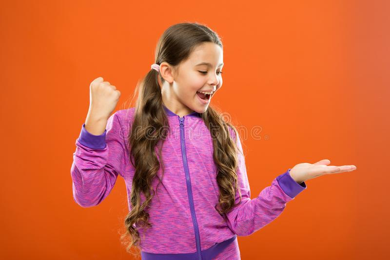 Product presentation. Kid happy face show something on open palm copy space. Girl demonstrate product. Advertisement and. Commercial concept. Promoting product stock image