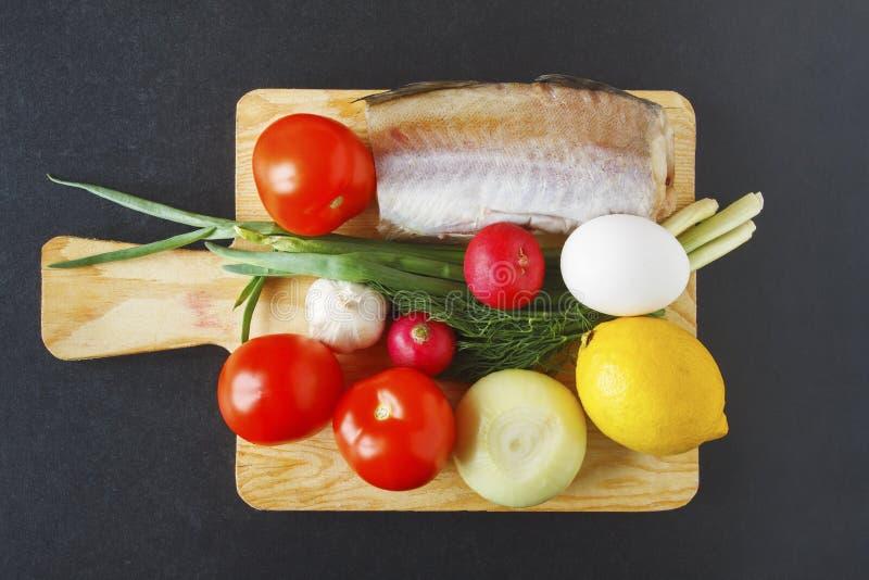 Product voor gezonde evenwichtige schotel op zwarte achtergrond wordt geplaatst die Vers organisch groenten en vissenstuk op sche stock foto's