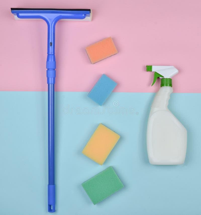 Producten voor het schoonmaken van glasvensters Sponsen, vensterzwabber, sproeierreinigingsmiddel op een blauwe roze pastelkleura stock foto