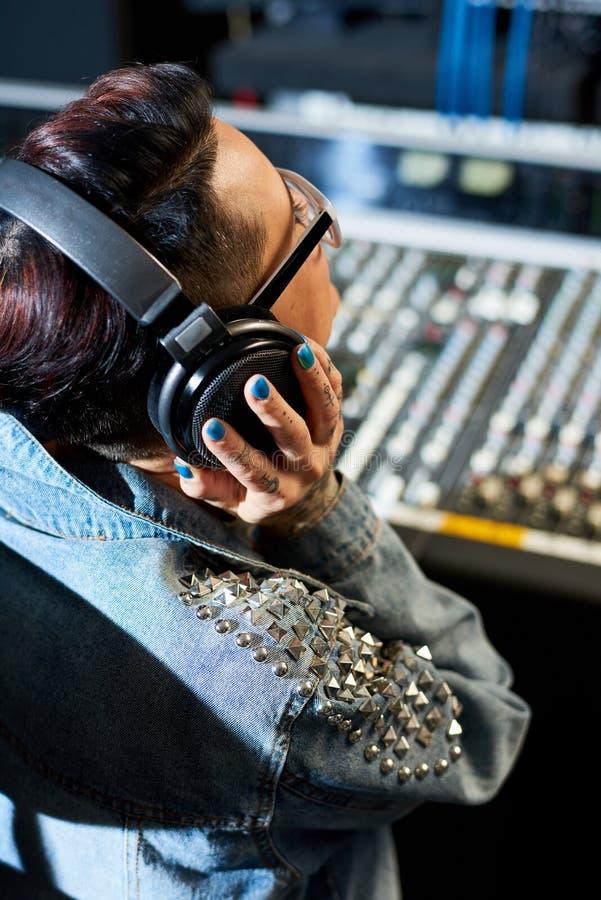 Producteur écoutant la voie audio dans le studio images libres de droits