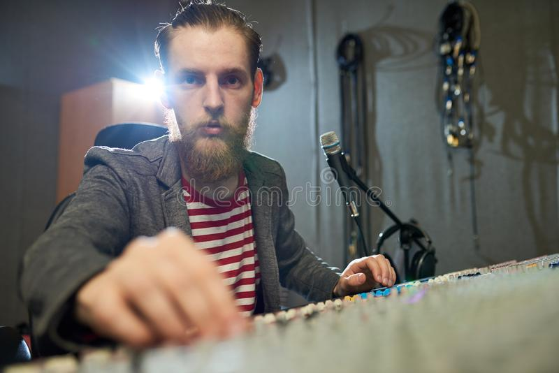 Producteur barbu travaillant à la console dans le studio photographie stock