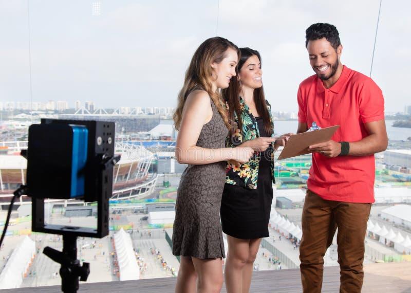 Producteur de télévision parlant avec les présentateurs féminins au sujet de l'exposition de TV image libre de droits
