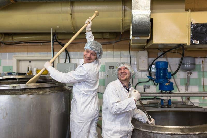 Productie van kaas in zuivelfabriek, arbeider twee stock fotografie