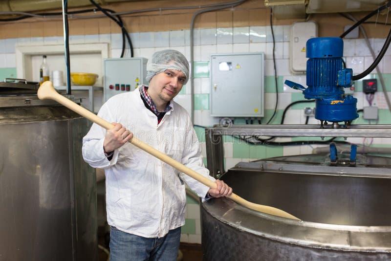 Productie van kaas in zuivelfabriek, de mengelingen van de arbeiderskaas royalty-vrije stock afbeeldingen