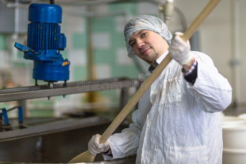 Productie van kaas in zuivelfabriek, de mengelingen van de arbeiderskaas royalty-vrije stock foto's