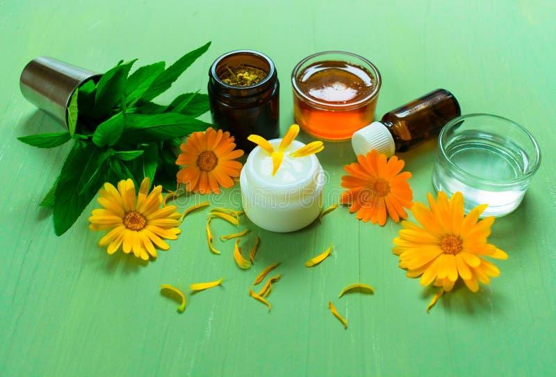 Productie van natuurlijke schoonheidsmiddelen Geneeskrachtige bloemen van calendula, kamille, munt en kruidentint, aromaolie, hon royalty-vrije stock afbeeldingen