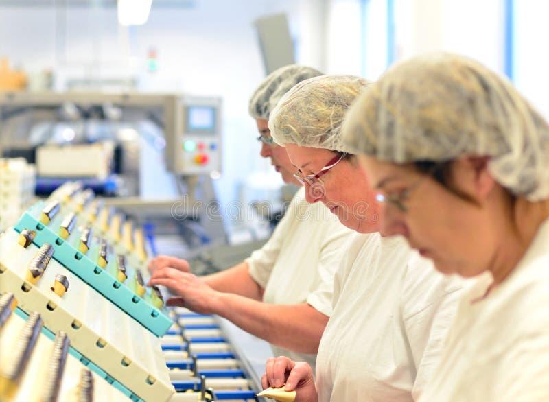 Productie van pralines in een fabriek voor de voedselindustrie - wome stock afbeeldingen