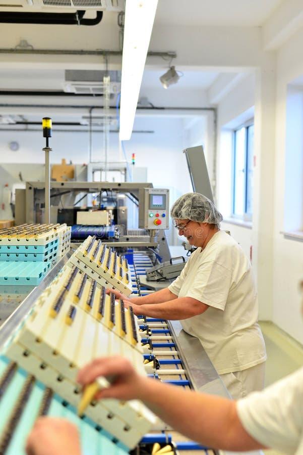 Productie van pralines in een fabriek voor de voedselindustrie - wome stock foto