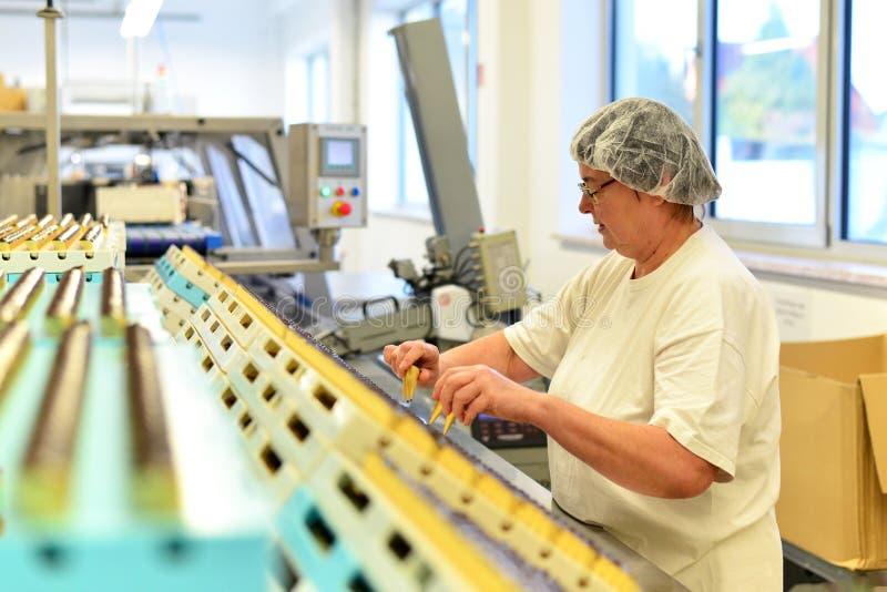 Productie van pralines in een fabriek voor de voedselindustrie - wome royalty-vrije stock afbeelding
