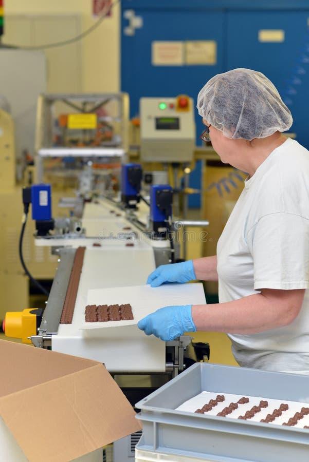 Productie van pralines in een fabriek voor de voedselindustrie - wome stock afbeelding