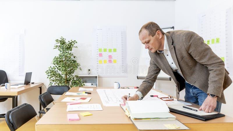 Productiemanager die weg op de herziene tekeningen van het productieontwerp ondertekenen stock foto's